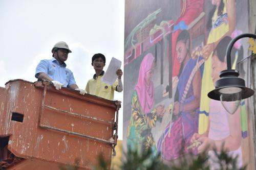 中国侨网蔡文涛向纳斯里(左)讲解巨型壁画的构图与含义。(马来西亚《星洲日报》)